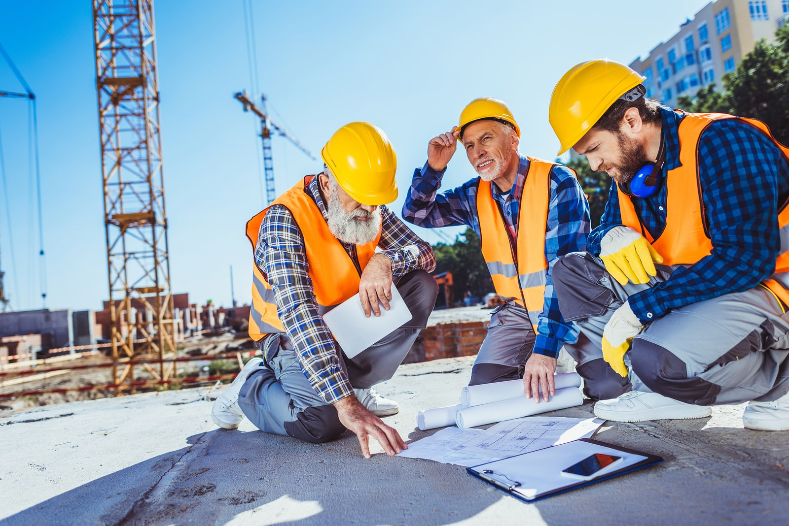 Three construction workers in uniform sitting on concrete at construction site examining building plans