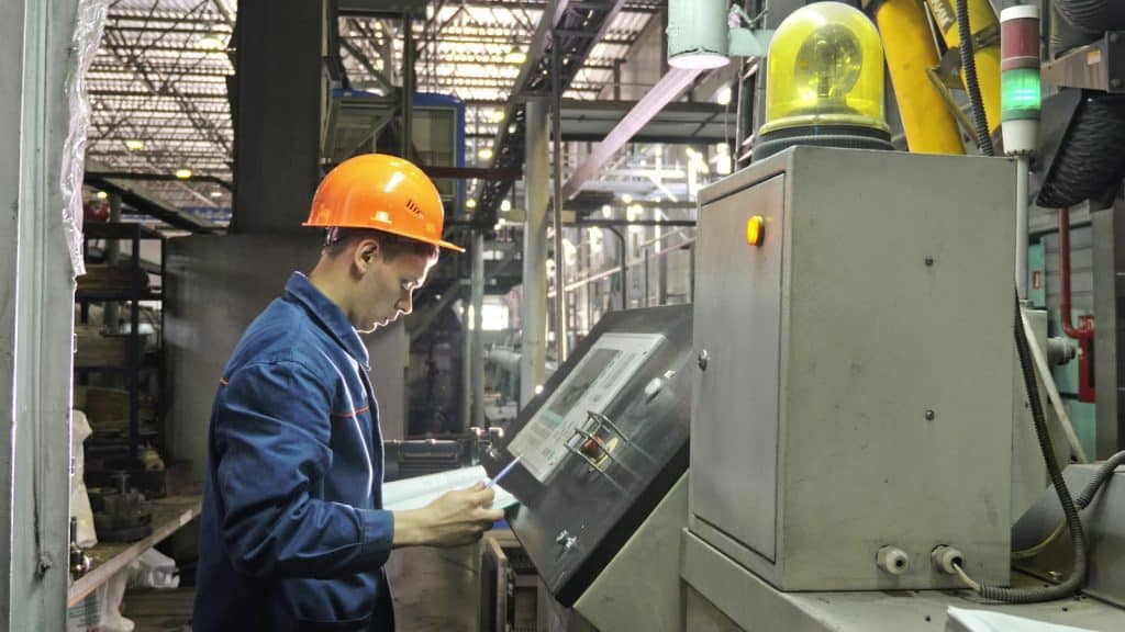 RUSSIA, ANGARSK - JUNE 8, 2018: Operator monitors control panel of production line. Manufacture of plastic water pipes of the factory. Process of making plastic tubes on machine tool with the use of water and air pressure.