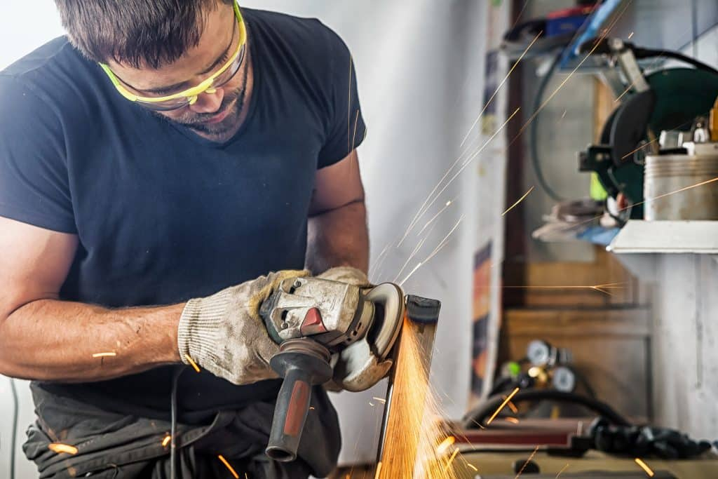 A man welder in a black T-shirt construction gloves hard works and brews grinder metal an angle grinder in the workshop on a wooden table
